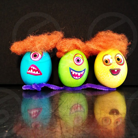 yellow green and blue egg figures with orange hairs photo