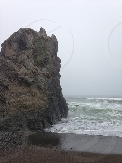 gray rock formation along beachfront photo