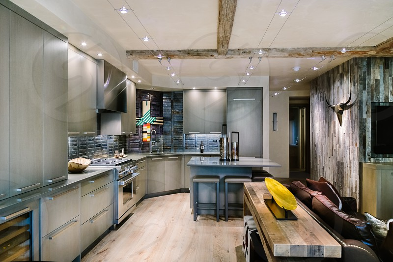Modern kitchen grey gray interior design slab cabinet mountain home wood beam rustic reclaimed bright stainless bar barstool built-in refrigerator L-shape island open concept open kitchen open living room photo