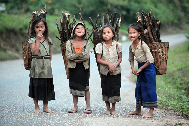girls with fire wood near the Village of Muang Phou Khoun on the Nationalroad 13 on the way from Vang Vieng to Luang Prabang in Lao in southeastasia. photo