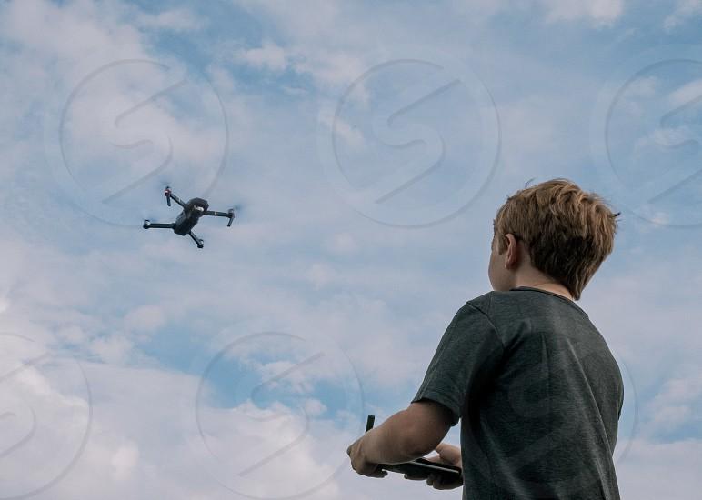 A boy flying a drone/UAV.  photo