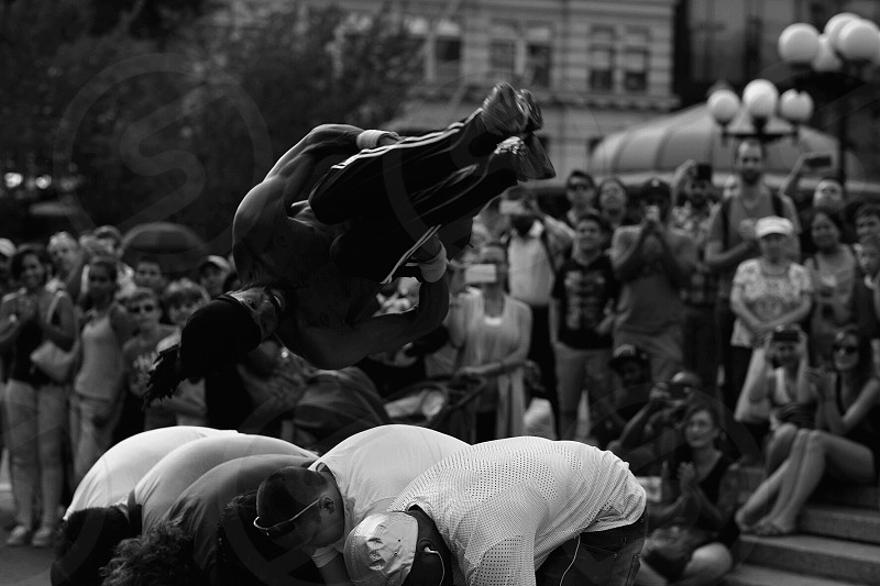 gray scale photo of people doing acrobatic photo