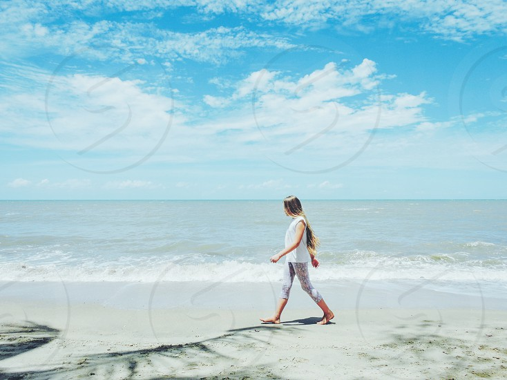 Girl walking empty beach tropical one person alone horizon sand ocean sea water shore long hair wind summer holiday travel destination traveling fun holidays sky clouds leisure activity casual Cairns Australia Australian  photo