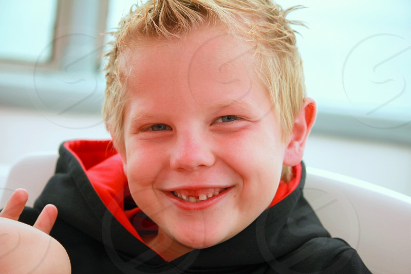 boy in black and red hoodie smiling photo