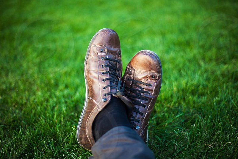 Two legs in leather shoes resting on fresh grass. photo