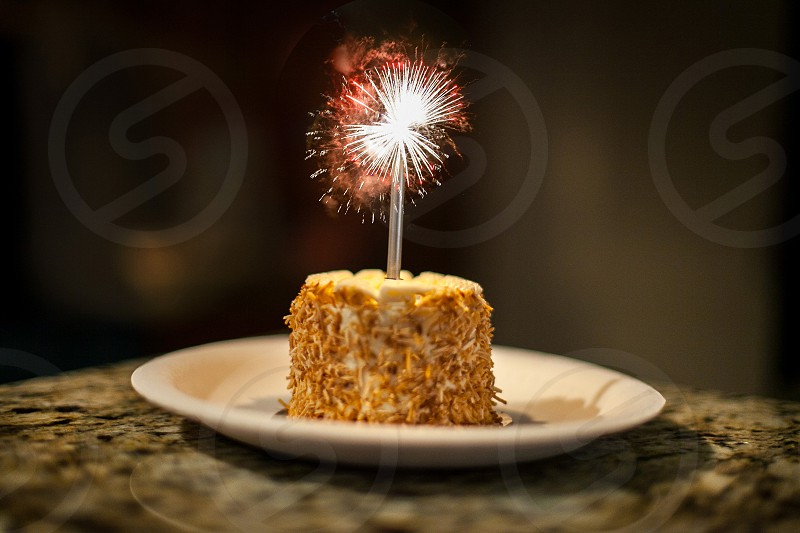 A small birthday cake with a single candle and a tiny fireworks display on top.  Coconut yellow silver red explosion blast firecracker plate granite countertop kitchen celebrate cheer bright blended reality photo