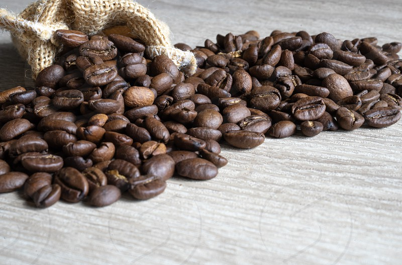 Roasted brown coffee beans  with small sack  on wooden table background photo