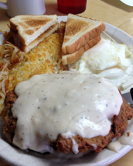 Chicken fried steak covered with gravy served with fried eggs hashbrowns and toast photo