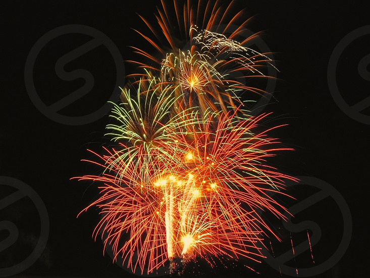 Multiple red green yellow white and orange bursts of fireworks exploding simultaneously against black sky; fireworks explosion celebration holiday happiness colorful spectacular. photo
