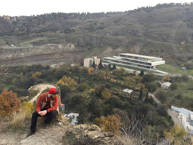 man in orange zip-up letterman jacket and black pants sitting on hill facing white concrete building photo