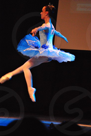woman wearing white and blue ballet dress dancing on stage photo