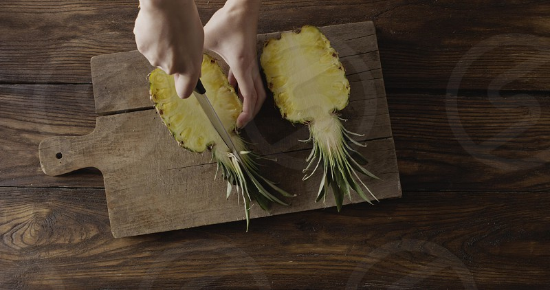 Woman's hands are cutiing the halves of fresh yellow natural tropical pineapple in a quater. Four parts of fruit on a cutting board on a wooden table. Top view. Motion 4K UHD video 3840 2160p. photo