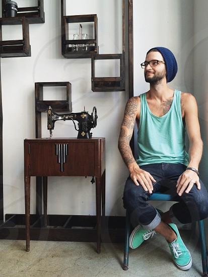 man in jeans and teal shoes and tank near vintage sewing machine table navy knit cap cube wall shelves photo