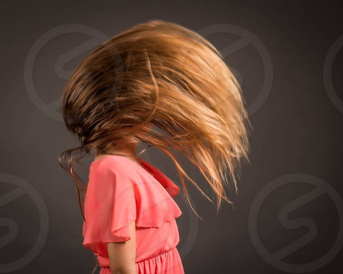 girl with brown long hair doing hair back flip photo