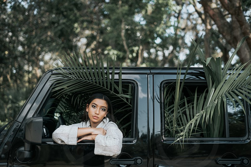 Fashion model sitting in car full of plants photo