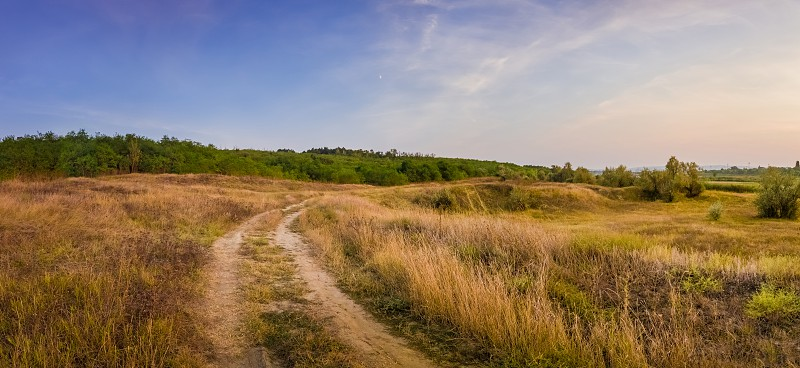 Idyllic autumn rural panorama with and a country track across a meadow with dry grass and hay. Beautiful evening scene peaceful sunset light over the steppe vegetation. photo