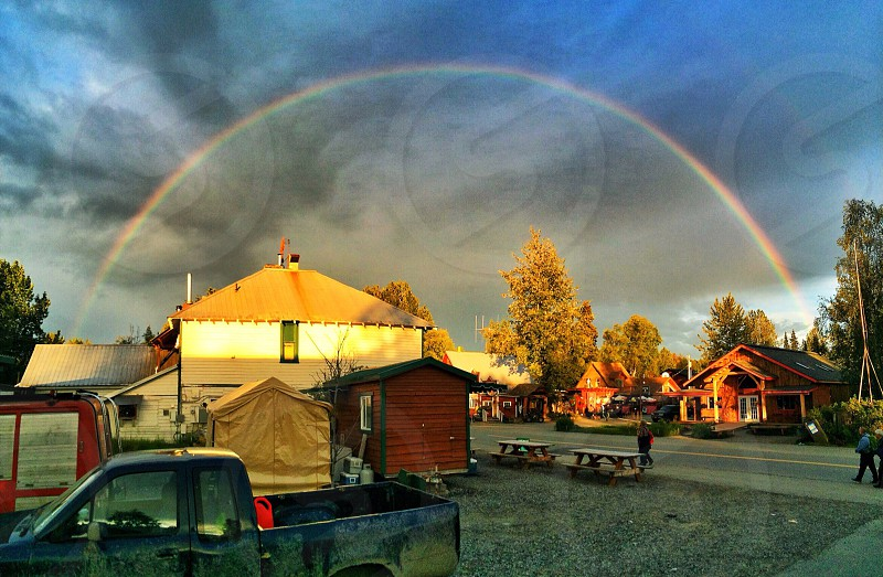 two picnic tables beside wooden shed and enclose canopy tent with a view of rainbow photo