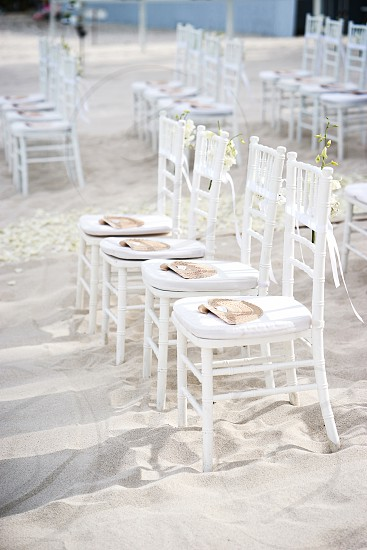 Side view of white chiavari chairs in a row with cone of roses petal and ribbon on the back side Chinese wooden folding fan on the seat as souvenir. Beach wedding venue arrangement. photo