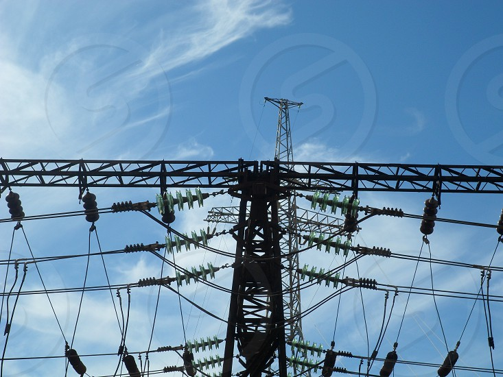 worms eye view of transmission tower under white and blue cloudy sky during daytime photo