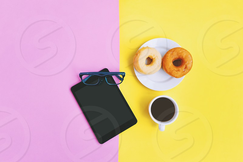 Modern home office workplace at coffee time A cup of coffee donuts eye glasses and tablet on yellow pink pastel background with copy space photo