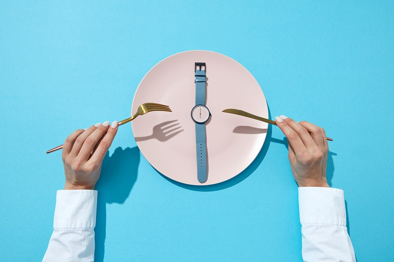 White plate whatch with blue band shows six o'clock served knife and fork in a girl's hands on a blue background place for text. Time to eat and diet concept. Top view. photo