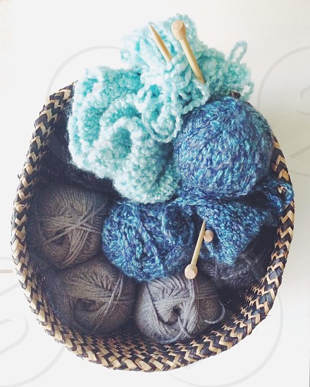 A knitting basket filled with skeins of yarn and knitting needles.  photo