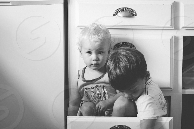 two babies wearing printed shirt inside a drawer chest photo