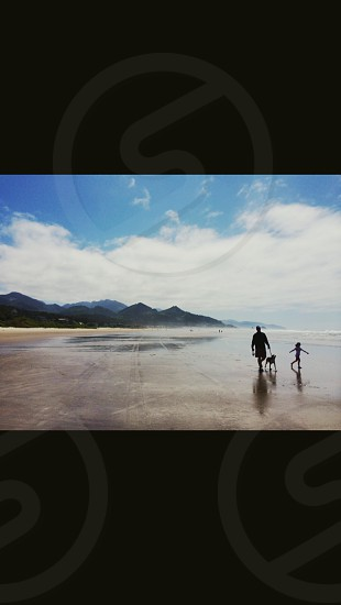 person holding dog together with a child on ground near mountains photo