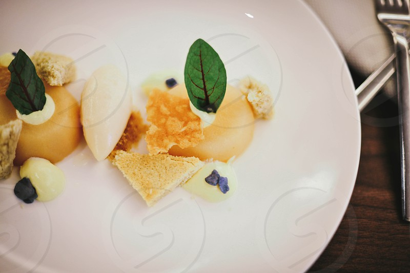 gourmet dessert with green leaf garnish on a white plate photo