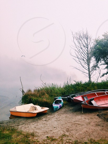 blue kayak beside red wooden boat photo