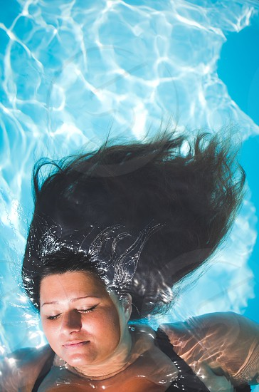 Woman with long black hair floating in a pool with the sun shining. photo