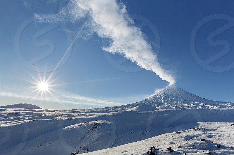 Winter view of eruption active Klyuchevskoy Volcano (Klyuchevskaya Sopka) and sun rays on beautiful blue sky on frosty day. Beautiful volcanic landscape of Kamchatka Peninsula in Russian Far East. photo