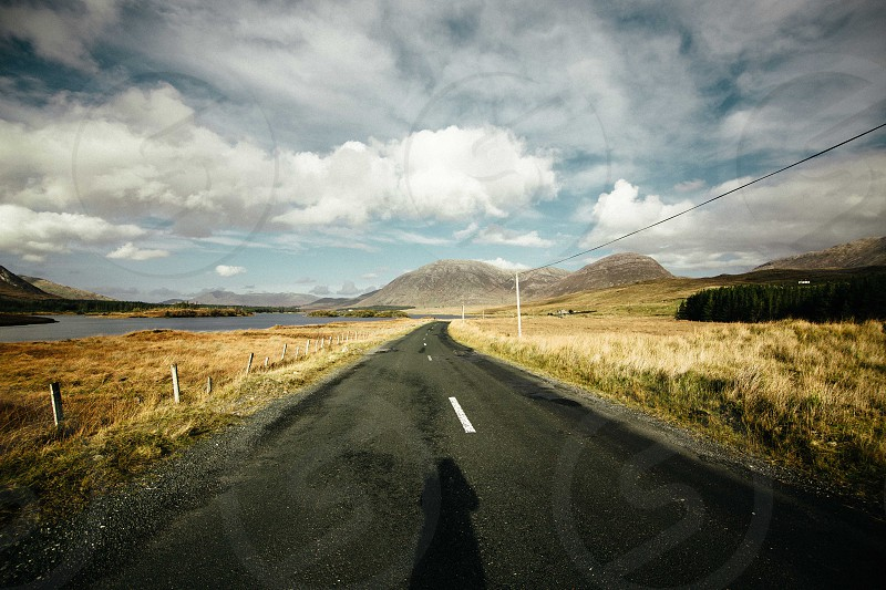 Ireland landscape road lake shadow sky clouds photo