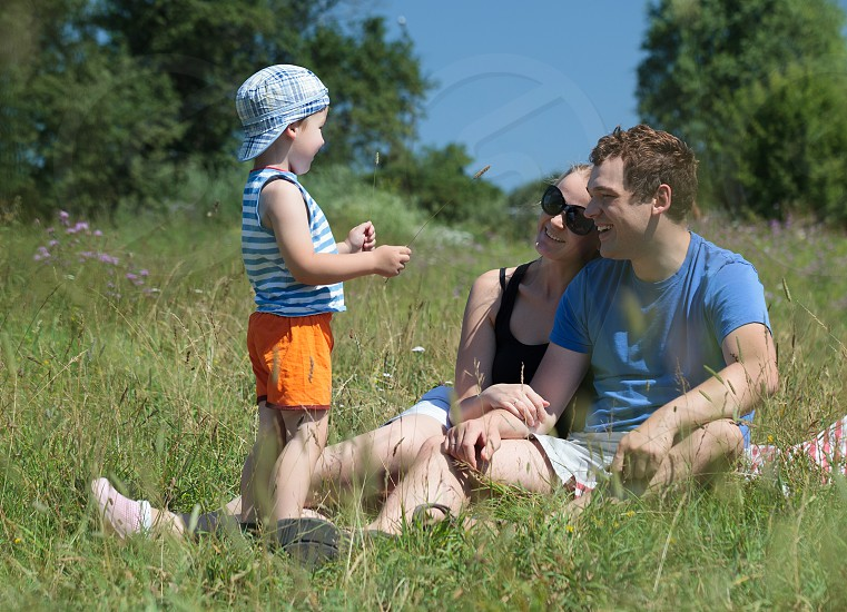Young parents and son on the meadow on a hot summer day. Happy couple sitting on the grass and looking at the kid. Outdoor family activity photo