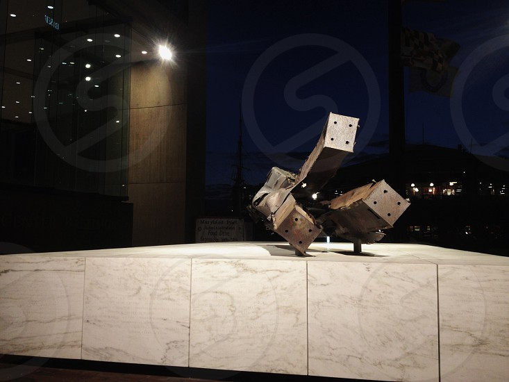 9/11 Memorial at Baltimore World Trade Center Inner Harbor (9/11 sculpture September 11 memorial marble steel night) photo