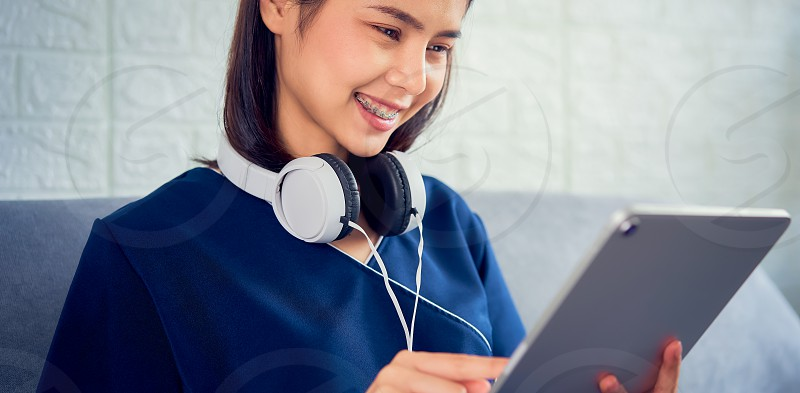 Happy young Asian woman wearing white headphones listening to love music and using tablet on the sofa in house. photo