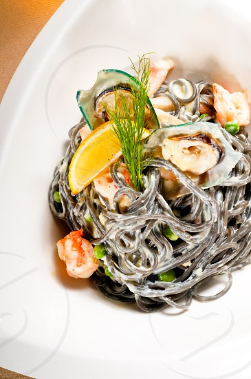 fresh seafood black squid ink coulored spaghetti pasta tipycal italian food photo