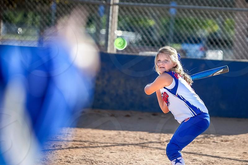 Pitcher throws a green softball / baseball while a girl at bat prepares to swing. photo