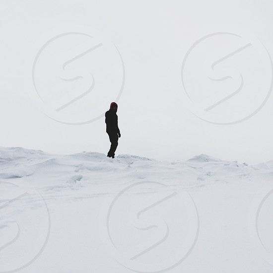 person in black jacket and black pants standing on snow covered field photo