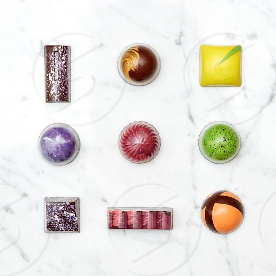 Assorted collection of chocolate candies and sweets isolated on a white marble background photo