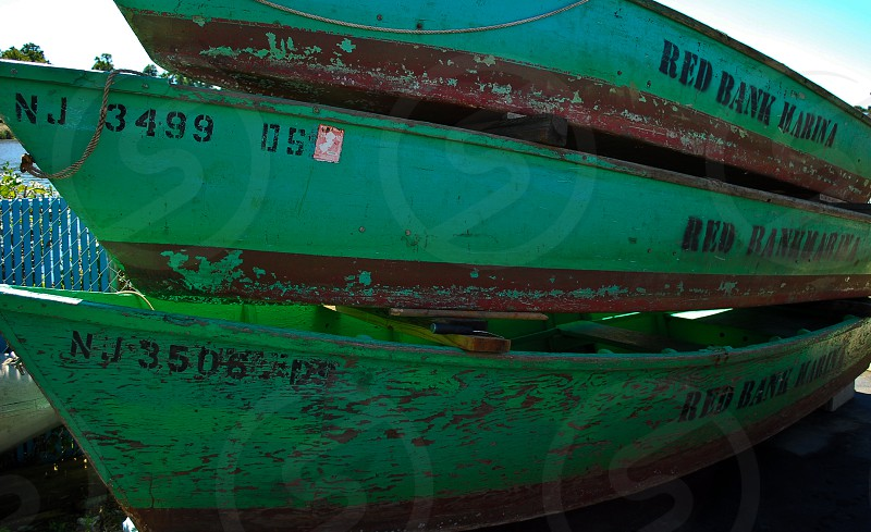 old beat up green boats in Red Bank New Jersey at a marina photo