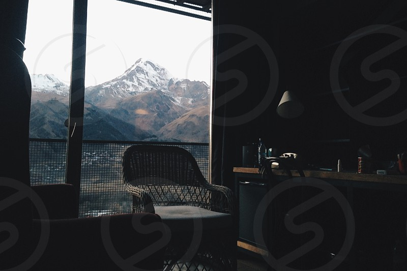 beige wicker armchair beside glass window with overlooking mountain photo