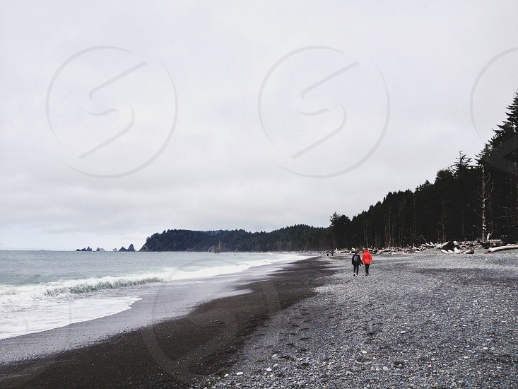 view of man and woman walking near the sea photo