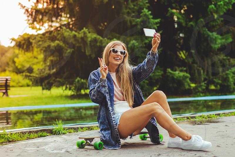 woman in pink shirt under blue denim jacket sitting on black skateboard taking selfie photo