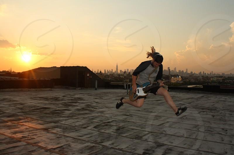 man playing electric guitar while jumping during sunset photo