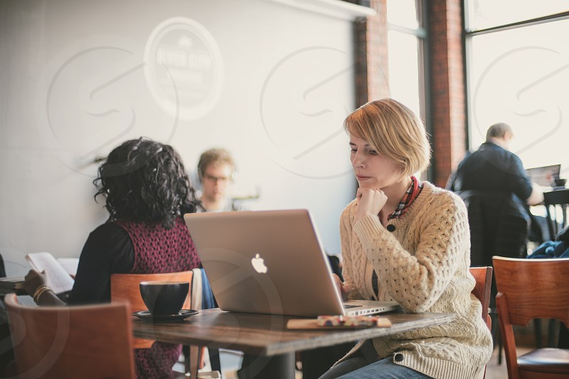 woman in beige cardigan using apple laptop photo