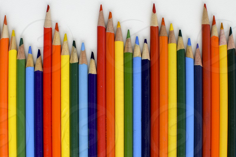 Uneven row of colored pencils on a white background photo