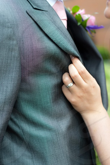 Brides ring hand holding Grooms jacket photo