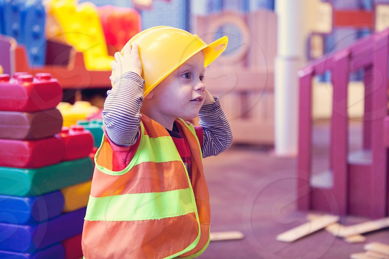baby in yellow construction hat and vest near large play blocks photo