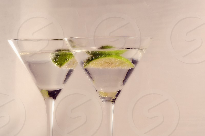 Two martini drinks with a twist of lime. photo